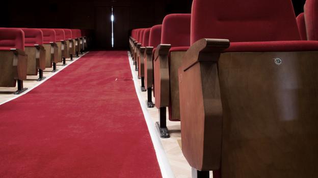 Zwei Reihen Konzertstühle, dazwischen ein roter Teppich.