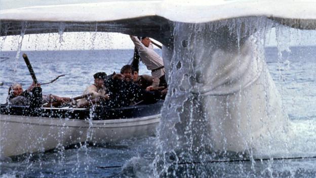 Ein weisser Wal und im Hintergrund ein Holzboot mit Männern an Bord.