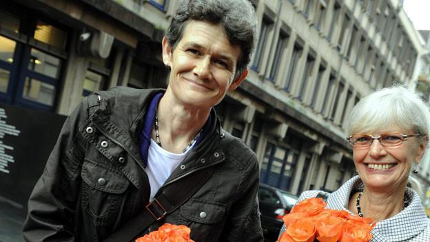 Esther Wyler und Margrit Zopfi stehen mit Blumen in der Hand vor dem Zürcher Bezirksgericht im Jahr 2009.