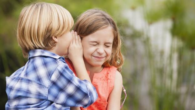 Ein Junge flüstert einem Mädchen etwas ins Ohr.