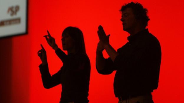 Zwei Menschen sprechen Gebärdensprache. Sie sind auf der Bühne im Schatten.