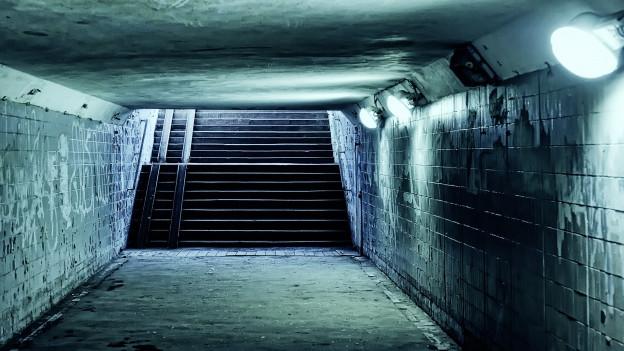 Eine mit kaltem Licht beleuchtete Unterführung mit einer aufwärts führenden Treppe am Ende.