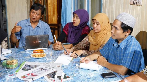Zwei indonesische Männer und zwei indonesische Frauen sitzen an einem Tisch.