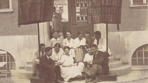 """Menschen sitzen auf einer Treppe vor einem Haus. Im Hintergrund ein Plakat, auf dem """"Völkerkundliche Ausstellung"""" steht."""