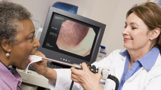 Eine Doktorin untersucht die Stimmbänder einer Frau.