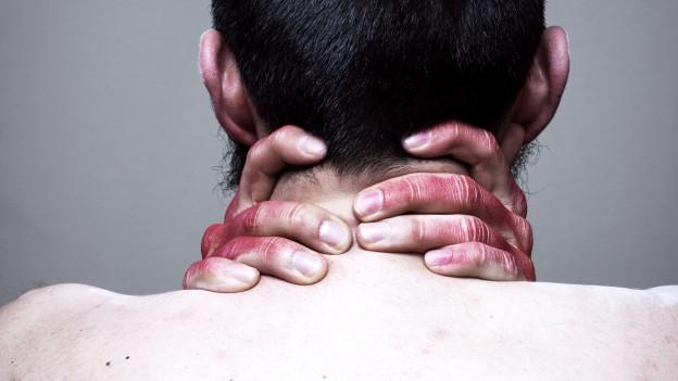 Ein Mann sitzt mit nacktem Rücken zur Kamera, seine Finger sind rot eingefärbt.