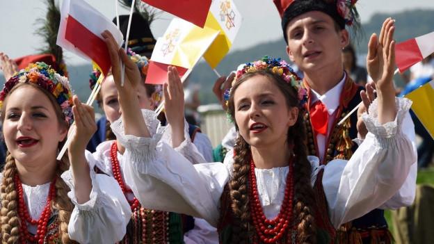 Junge Menschen in Trachten an einem Volksfest in Polen.
