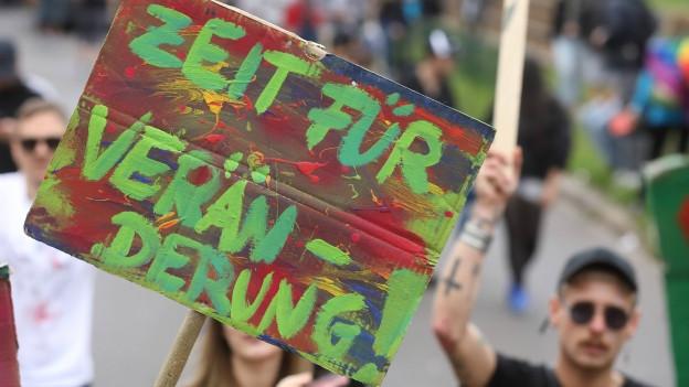 Buntes Plakat Zeit für «Veränderung!» auf einer Kundgebung
