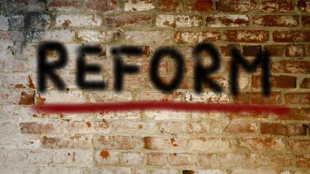 Das Wort Reform steht auf einer Backsteinwand