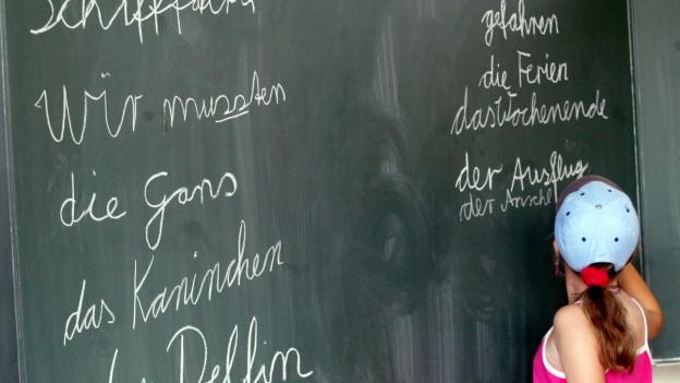 Mädchen schreibt mit Kreide Wörter an eine Tafel