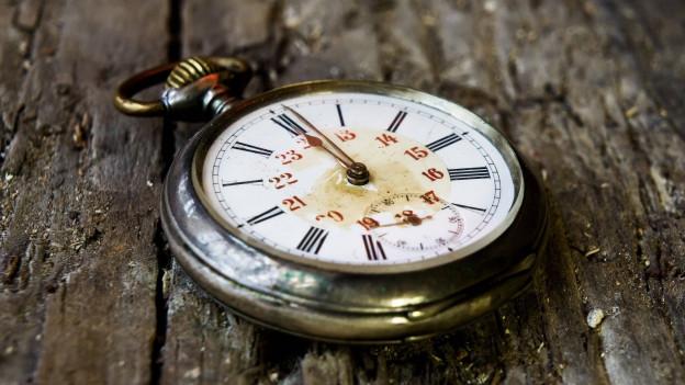 Eine alte Taschenuhr auf einem Holztisch