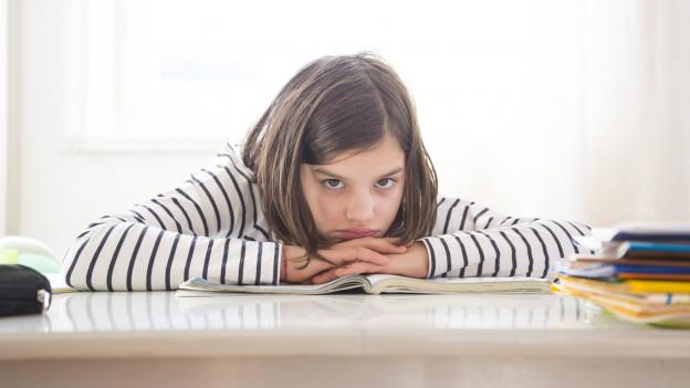 Mädchen sitzt vor seinen Heften am Tisch und langweilt sich