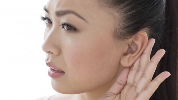 Eine Frau greift sich ans Ohr, um besser hören zu können