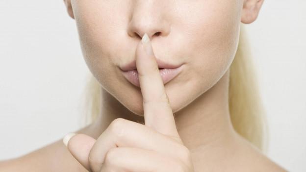 Eine Frau hält den Finger vor den Mund