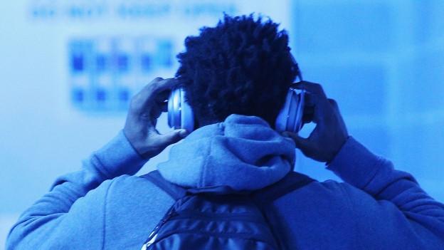 Ein Junge trägt Kopfhörer