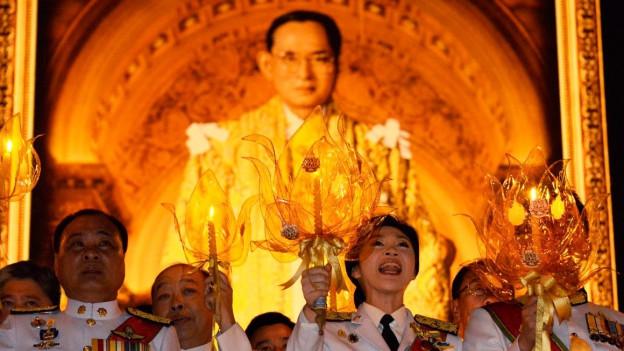 Im Vordergrund halten Menschen in Uniform Kerzen hoch. Dahinter hängt das beleuchtete Bild des Königs.