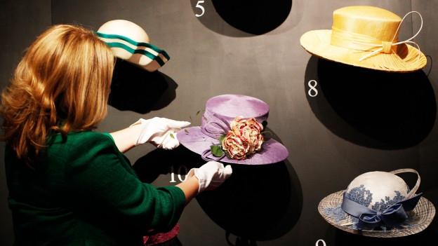 Frau steht vor einer Wand mit modischen Hüten.