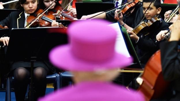 Queen Elizabeth II. steht vor einem Orchester.