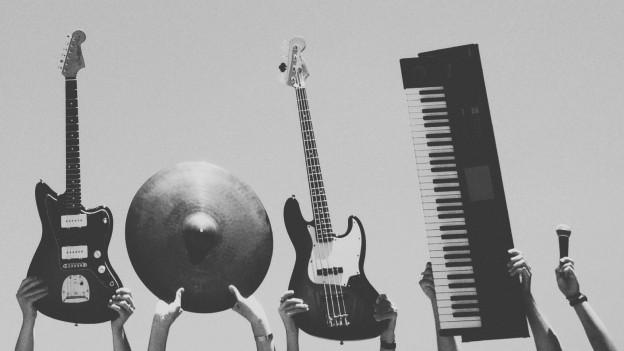 Diverse Musikinstrumente werden in die Luft gehalten.