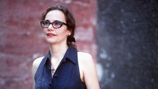 Eine Frau mit langem, krausem Haar und markanter Brille schaut in die Ferne.