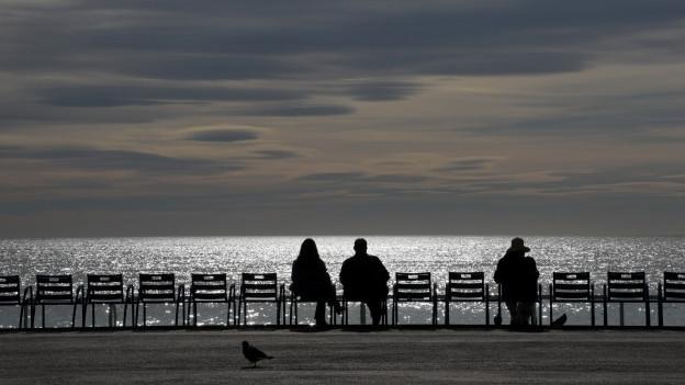 Drei Leute sitzen auf aneinandergereihten Stühlen am Ufer und schauen ins Meer.