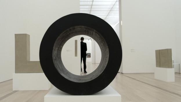 Ein Mann wird symetrisch von einer runden Skulptur im Museum umrahmt.