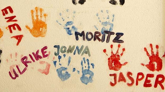 Farbige Abdrücke von Kinderhänden sind mit den entsprechenden Vornamen versehen