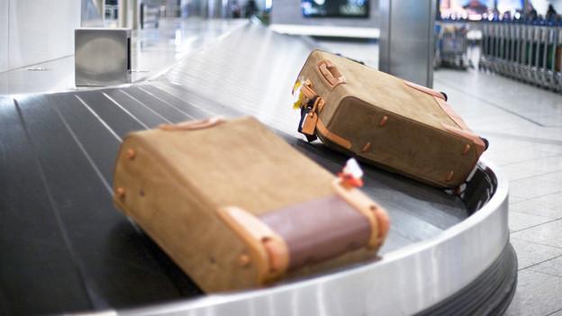 Zwei Koffer auf dem Förderband am Flughafen.