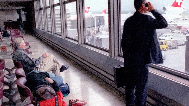 Wartehalle in einem Flughafen. EIn Mann steht am Fenster und telfoniert.