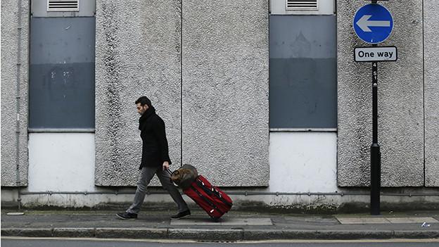 Ein Mann mit Rollkoffer geht einer Strasse entlang