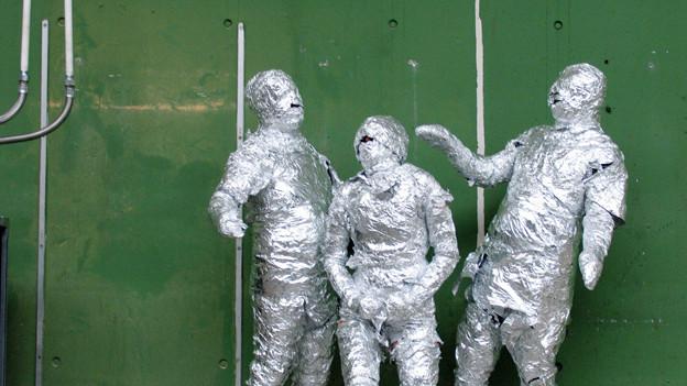 Drei Personen, komplett in Alufolie eingewickelt, stehen vor einer grünen Wand.