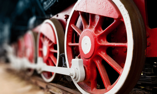 Eine Nahaufnahme von den Rädern und Schienen einer Dampflok.