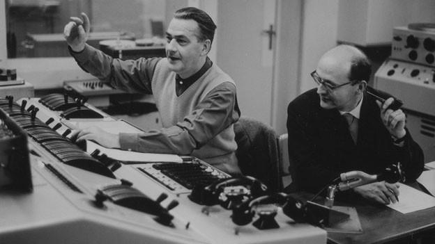 Robert Egger am Regiepult gibt Anweisungen, Bearbeiter Hans Rudolf Hubler studiert das Manuskript.