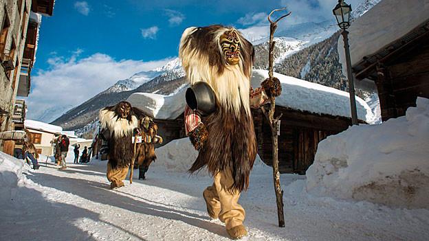 Lötschentaler Masken im verschneiten Dorf