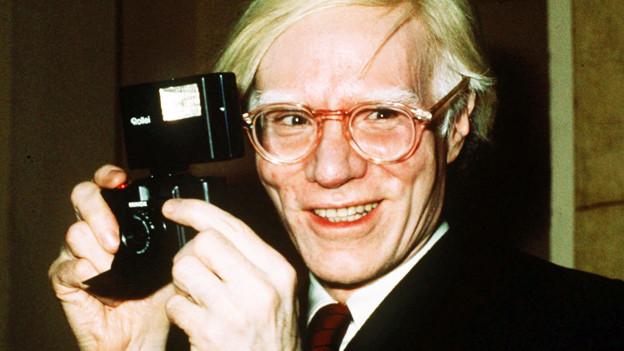 Andy Warhol mit einer Kamera.
