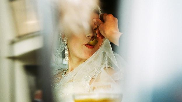 Eine Hand löffelt einer Braut Honig in den Mund.