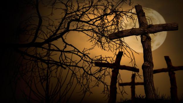 Dunkle Grabkreuze in der Nacht im Vollmond