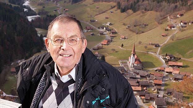Der Buchautor Leo Buchs - im Hintergrund das Dorf Jaun