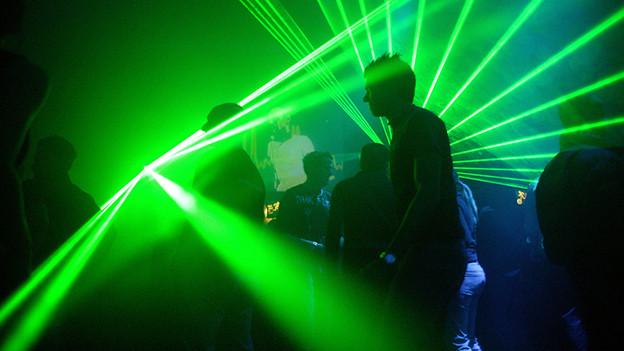 Menschen in einem Club zwischen grünen Laserstrahlen