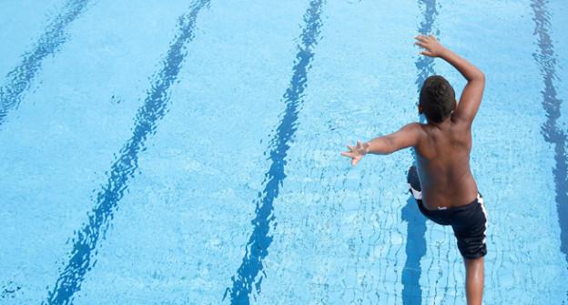 Kind springt in einen Pool.