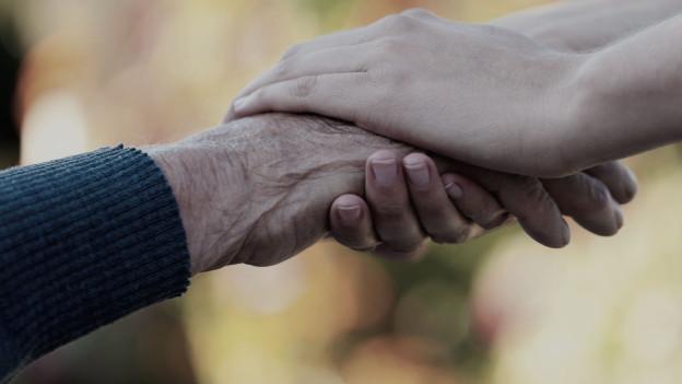 Alte und junge Hand halten einander.