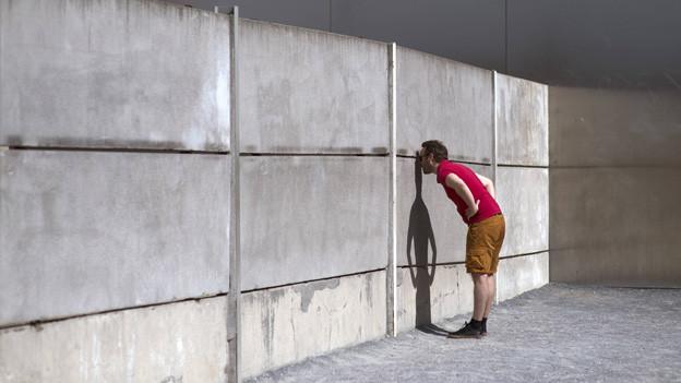 Ein Mann blickt durch einen Spalt in einem Reststück der Berliner Mauer.