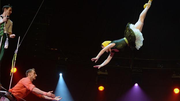 Frau schwebt frei in der Luft während einer Zirkusvorführung.