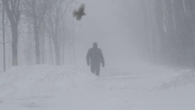 Mann geht durch einen Schneesturm.