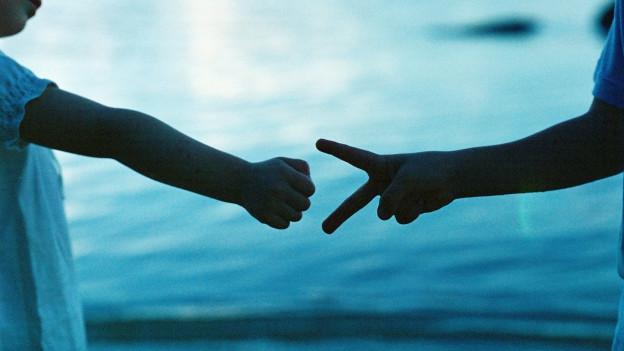 Zwei Kinder spielen am Ufer eines Gewässers «Schäri, Schtei, Papier»