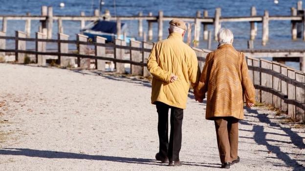 Zwei ältere Leute spazieren einem Pier entlang.
