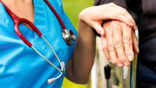 Eine Pflegerin legt einem Demenzkranken die Hand auf.