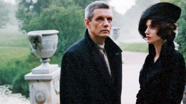 Ein Mann und eine Frau in edlen Kleidern stehen in einer Einfahrt zu einer Villa.