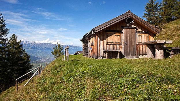 Eine Holzhütte auf einer Alp mit Blick übers Tal.