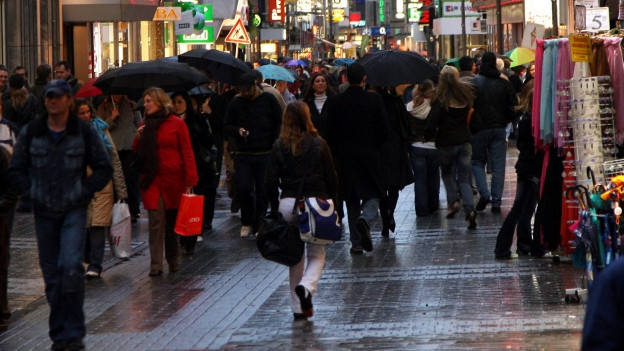 Menschen in einer Einkaufsstrasse in Köln.